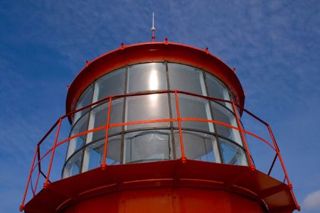 repulse: Red lighthouse`s lamp on the blue sky background