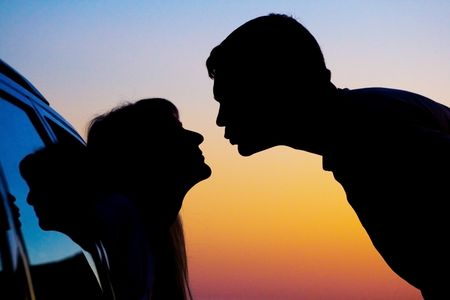 two Silhouettes of kissing people on sunset background photo