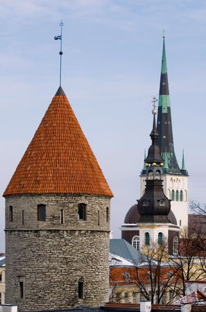 embrasure: view on fortifications and old church in center of old Tallinn Stock Photo