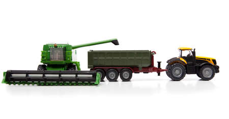 combine harvester: toys combine harvester and tractor with semi-trailer are isolated on white background Stock Photo