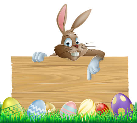 rabit: An Easter bunny character peeking over a wooden Easter sign pointing his finger down at space for your message  Surrounded by decorated chocolate Easter eggs