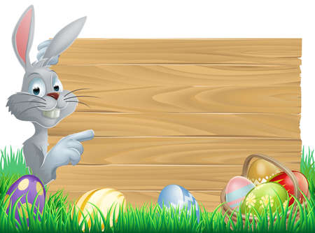White Easter rabbit bunny peeking round a sign and pointing, chocolate Easter eggs and basket in front