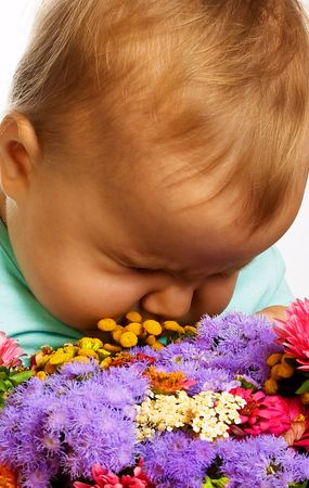 A little girl smelling flowers. photo