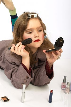 Cute naughty girl doing funny make-up. photo