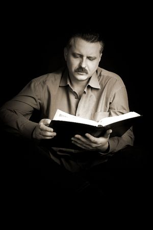A handsom man reading a big book in a dark room. photo