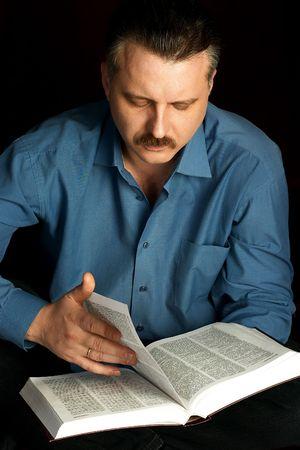handsom: Un hombre esposas leer un gran libro en una habitaci�n oscura.  Foto de archivo