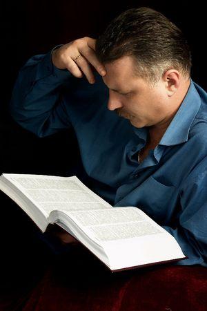 handsom: Un hombre del handsom que lee un libro grande en un cuarto oscuro. Foto de archivo