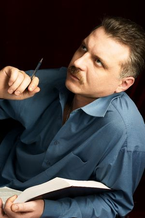 bookish: A handsom man reading a big book in a dark room.