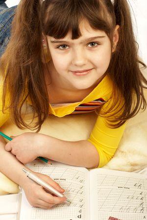 Funny girl doing school homework. photo