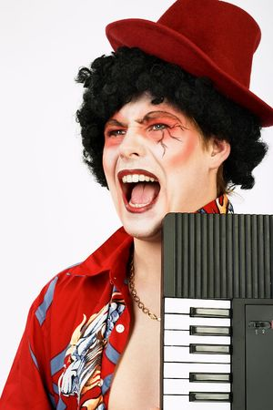 Funny screaming clown with a keyboard instrument. photo