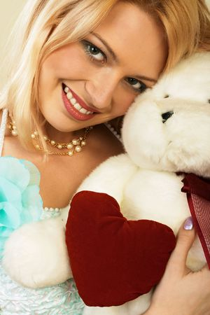 Smiling beautiful young woman in a nice evening dress holdind a Teddy Bear. Close-up. More images of this attractive model and other one you can find in my portfolio. WELCOME!!! WELCOME!!! WELCOME!!! Stock Photo - 331769