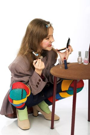Cute little girl in motherÂ's jacket and shoes doing funny make-up. photo