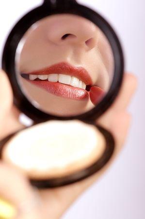 sensational: Pretty woman applying make up.