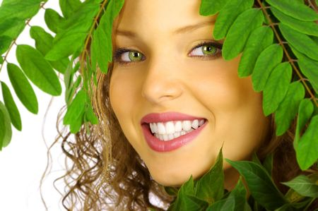 beautiful smiling young woman face among green leaves Stock Photo - 595930