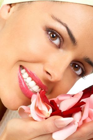Young pretty woman holding and smelling pink rose petals photo