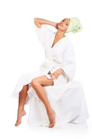 Beautiful young smiling woman in bathrobe. Isolated over white background photo