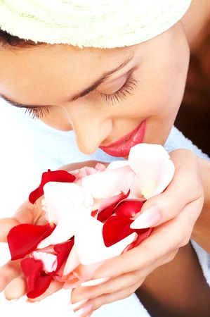 remedial: Young pretty woman holding and smelling pink rose petals Stock Photo