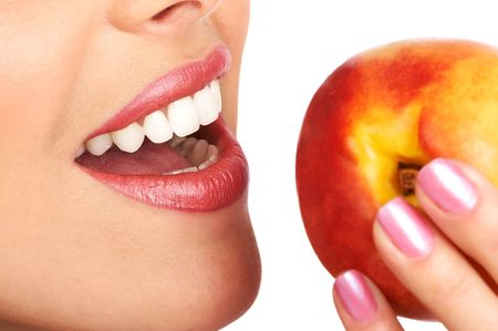 Beautiful young woman eating a peach. Isolated over white Stock Photo - 685165