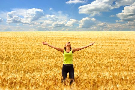 Happy young woman in the yellow field under blue sky photo