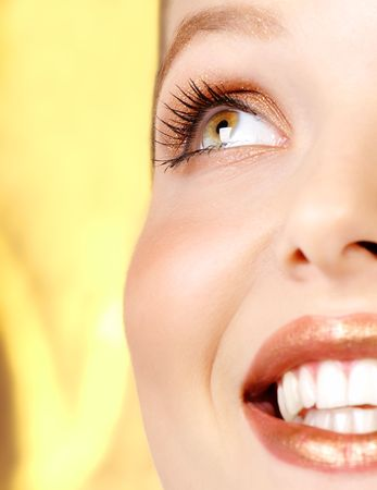 fem: Beautiful young woman face. Close up. Over golden background