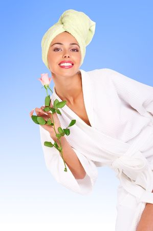Beautiful young smiling woman in bathrobe holding a flower. Isolated over white background photo