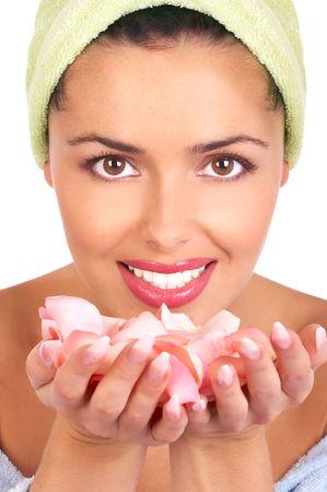 Mujer bonita joven que sostiene y que huele los p�talos color de rosa rosados Foto de archivo