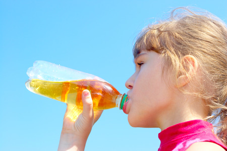 drink bottle: Young girl drinking a juce over blue sky