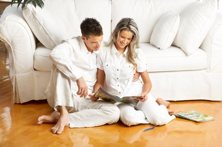 Young love couple reading magazine  in the comfortable apartment Stock Photo - 5493472