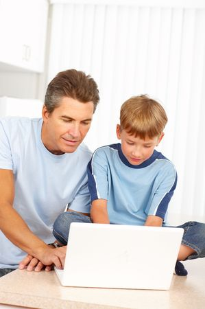 Happy family. Father  and son working with laptop. Stock Photo - 5487316