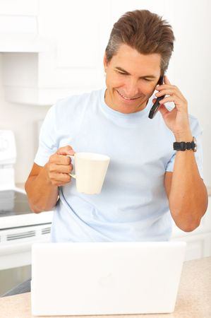 Young smiling man having lunch in  kitchen photo