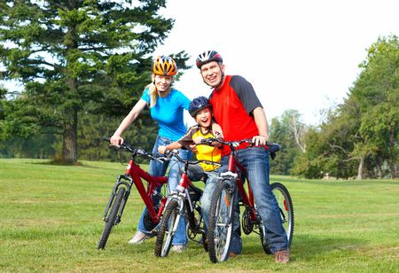 Happy family. Father, mother and son riding  in the park  photo