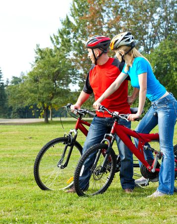 Happy smiling couple  riding  in the park Stock Photo - 5487337