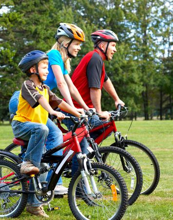 velo: Happy family. Father, mother and son riding  in the park