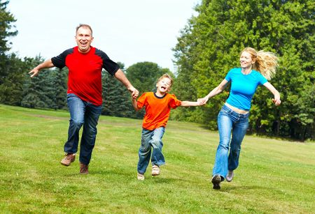 Happy family. Father, mother and sons running  in the park  photo