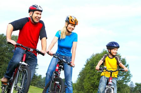 Happy family. Father, mother and son riding  in the park Stock Photo - 5487327