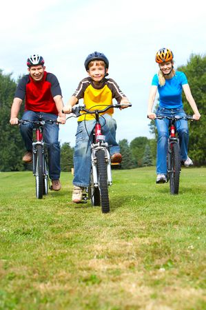 Happy family. Father, mother and son riding  in the park Stock Photo - 5487329