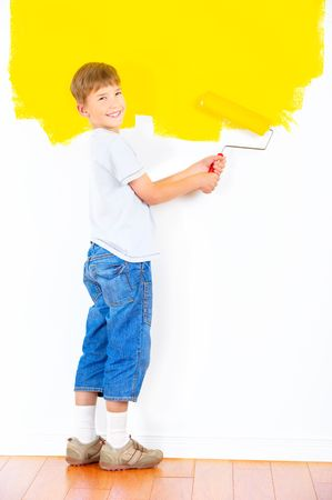 children painting: smiling boy painting interior wall of home.  Stock Photo