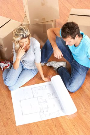 young couple sitting on the floor and looking at blueprints.  photo