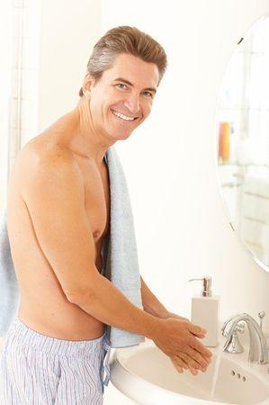 bathroom mirror: Smiling handsome man in the bathroom