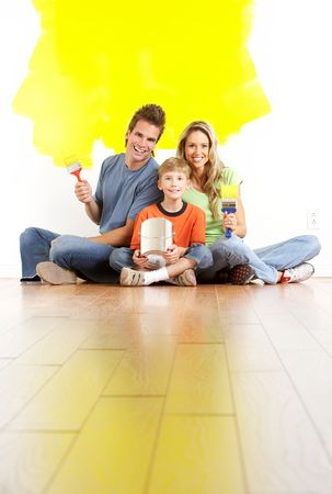smiling young family painting interior wall of home.   photo