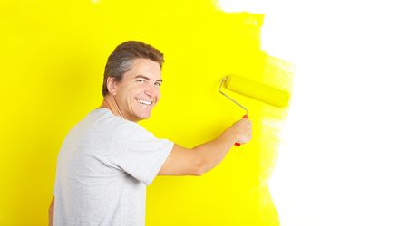 smiling handsome man near the painted  interior wall of home.   photo