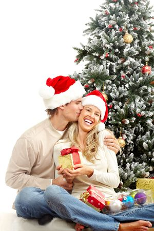 Young happy couple near  a Christmas tree. Isolated over white background Stock Photo - 5597749