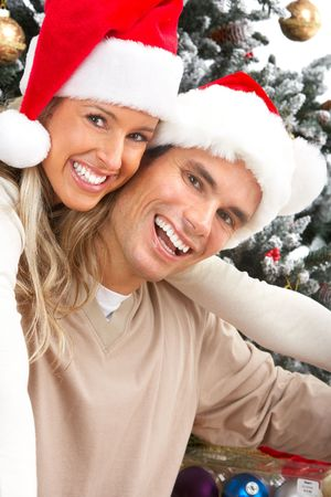 Young happy couple near  a Christmas tree. Isolated over white background Stock Photo - 5597744