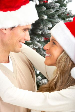 Young happy couple near  a Christmas tree. Isolated over white background Stock Photo - 5597741