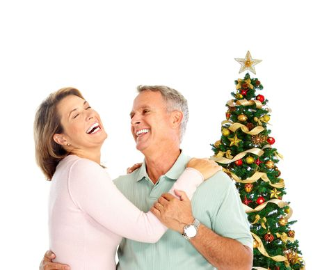 Elderly  happy couple near a Christmas tree. Isolated over white background  photo