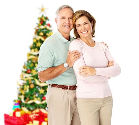 Elderly  happy couple near a Christmas tree. Isolated over white background  photo