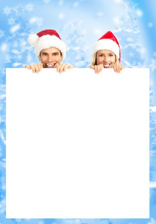 Young happy couple in Christmas hats. Over blue background photo