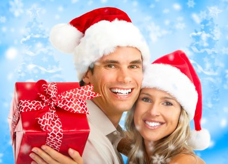 Young happy couple with a gift. Over blue background