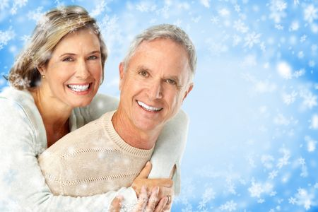 Elderly happy couple. Over snow blue background Stock Photo