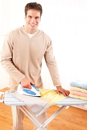Happy young handsome man ironing clothes. Housework  photo